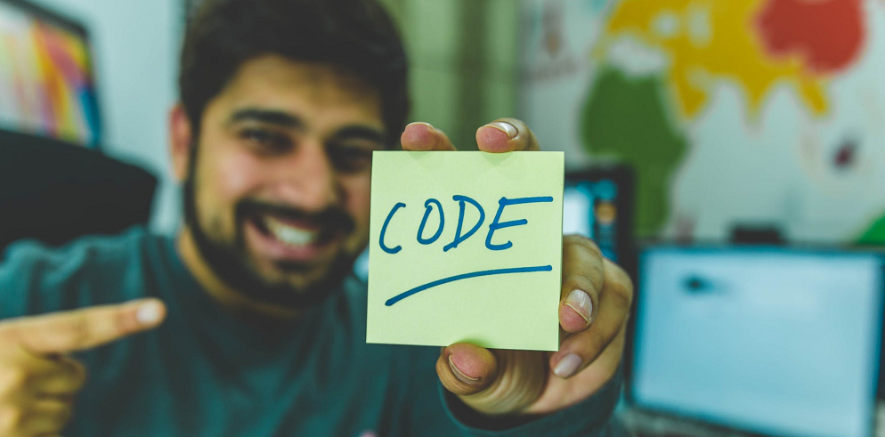 man holding a paper with code written on it